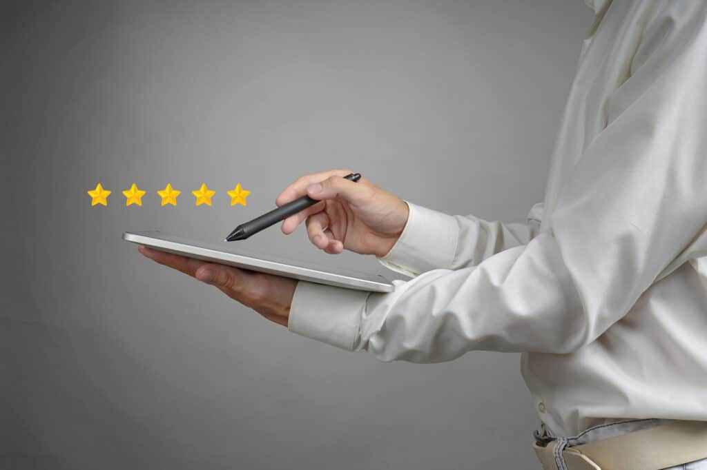 person holding tablet and a pen with five stars hovering above