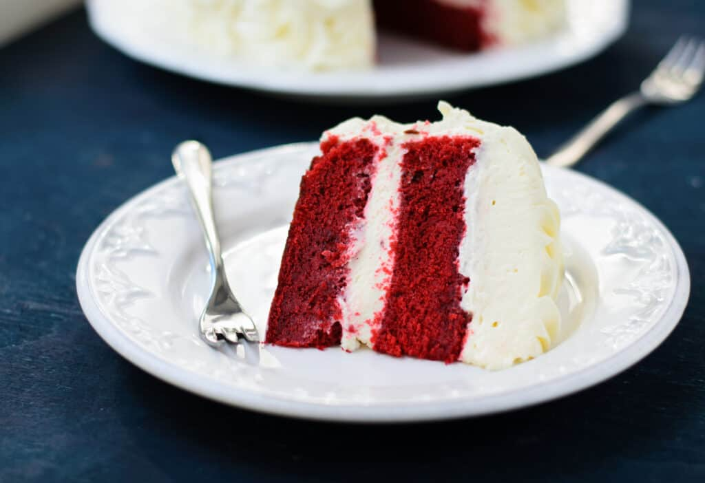 Red velvet cake sitting on a plate with a fork