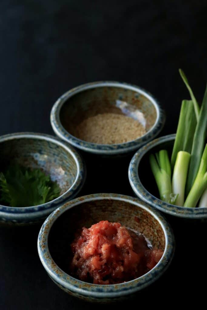 four bowls with different spices and ingredients in each