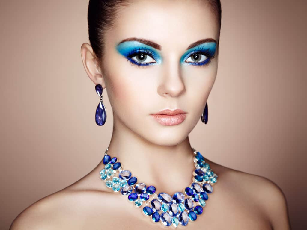 Portrait of women in blue makeup with matching blue necklace