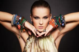 portrait of beautiful young brunette woman posing in rings and multiple bracelets on dark gray background