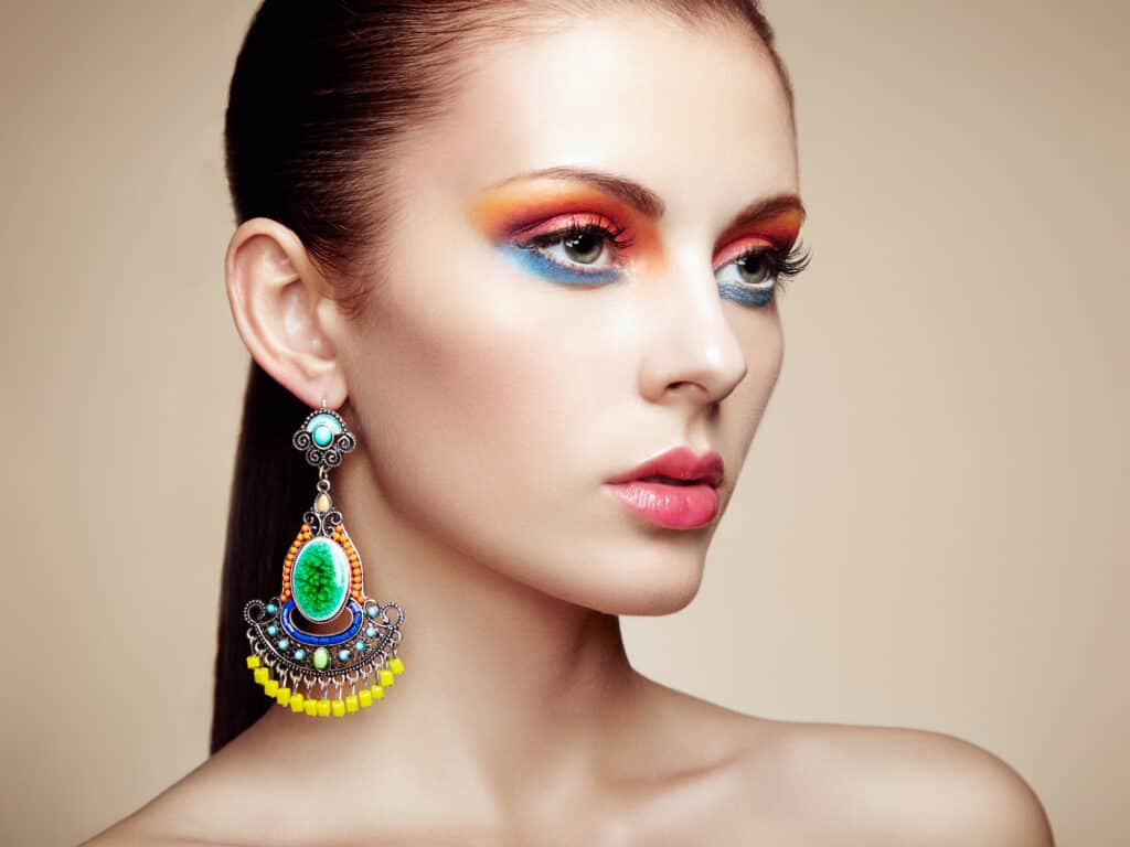 Portrait of women wearing bright colored earrings and bright colored matching makeup