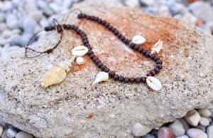 a bracelet with brown beads and small seashell charms sitting on a rock