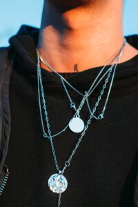 Person wearing layers of silver necklaces, one of which is stamped to add texture