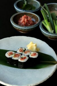 plate of sushi with two bowls in the background, each with different toppings