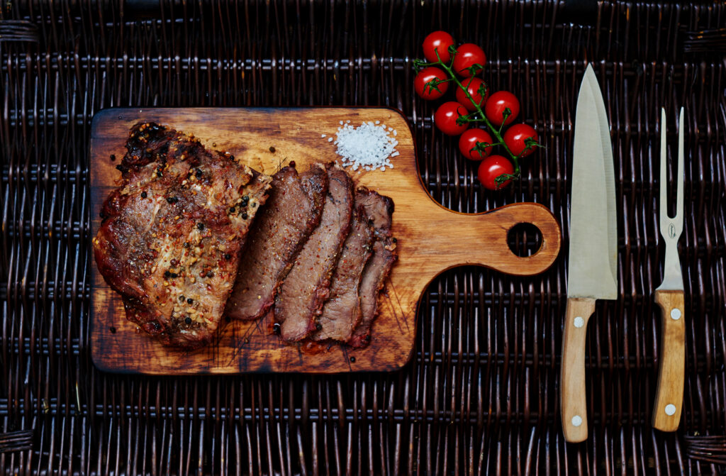Sliced steak sitting on a cutting baord next to knife and tomatoes