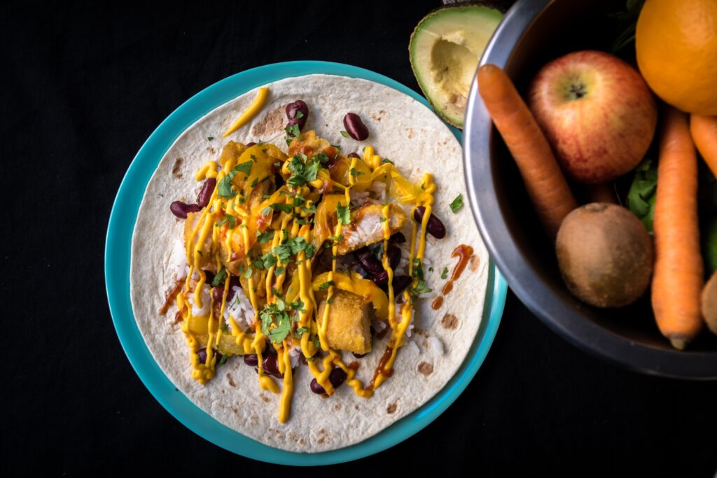 Plate of Mexican food sitting on black table
