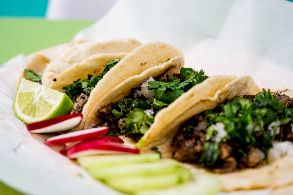 Three tacos sitting in a row on a plate