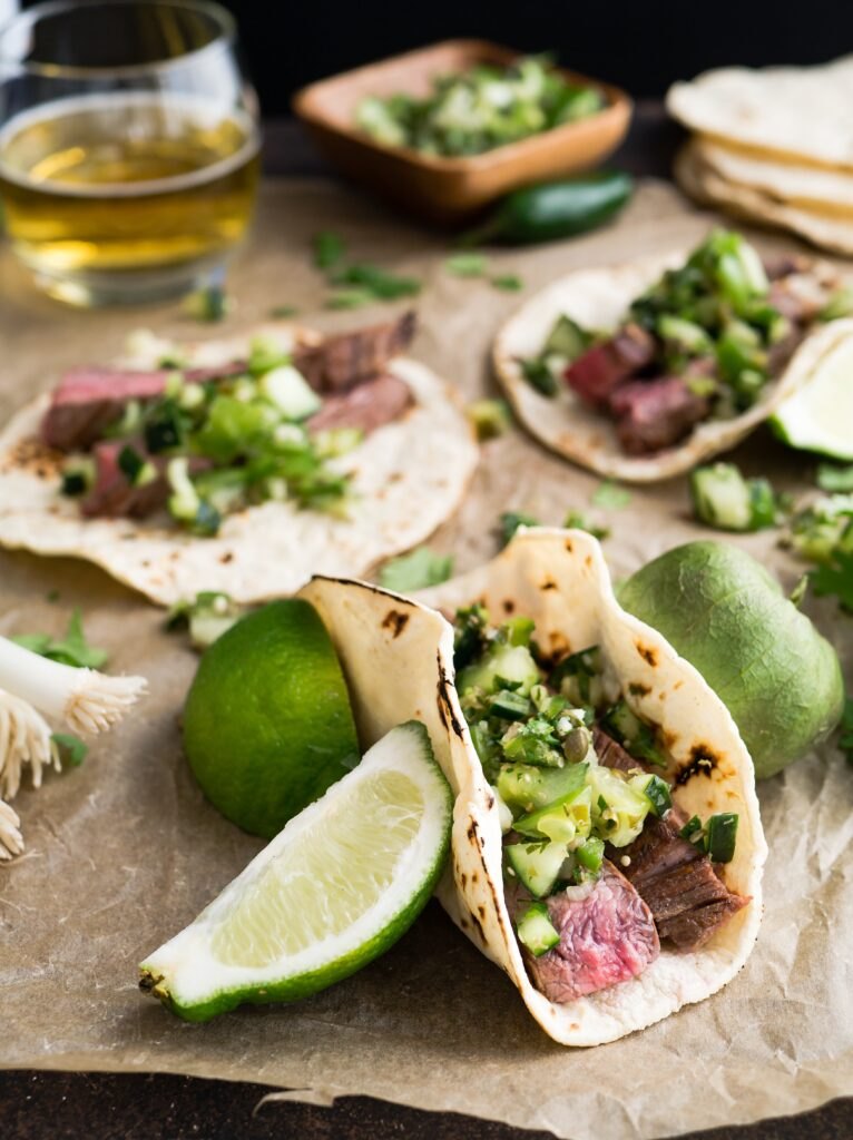 Multiple carnitas tacos sitting on a dining table