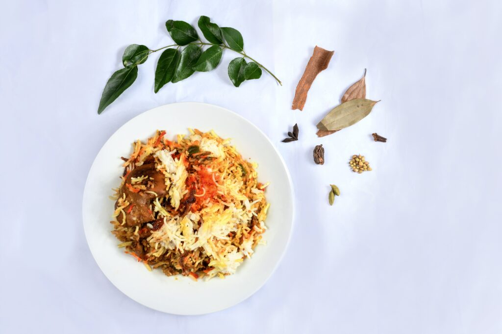 Bowl of curry and rise sitting on white table, surrounded by spices