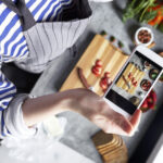 Person taking picture of food on phone from above