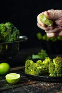 Chef sprinkling lime juice over a plate of broccoli