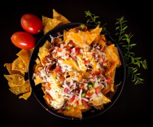 top view of a plate of nachos surrounded by different ingredients