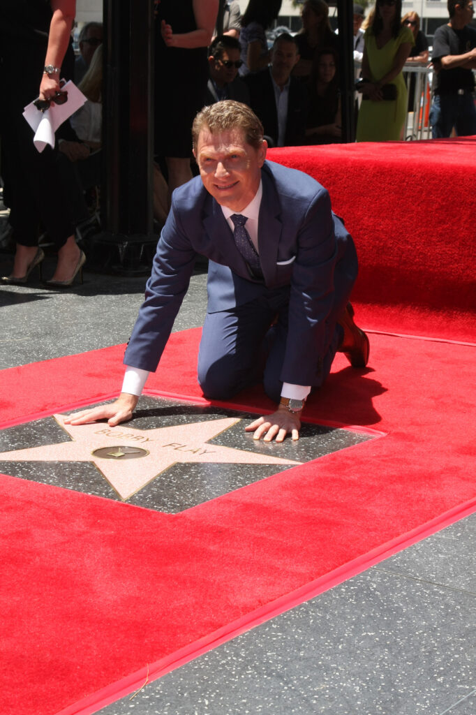 Bobby Flay taking a picture with his Hollywood Star at Hollywood Walk of Fame Ceremony.