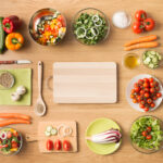 Creative vegetarian cooking at home concept with fresh healthy vegetables chopped, salads and kitchen wooden utensils, top view