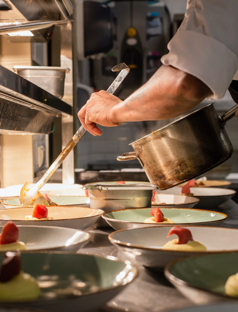 Chef putting final touches on multiple dishes