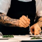 chef with tattoos placing final touches on a dish