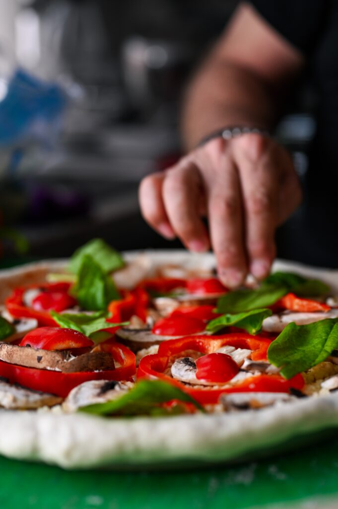 chef placing final touches on pizza dish