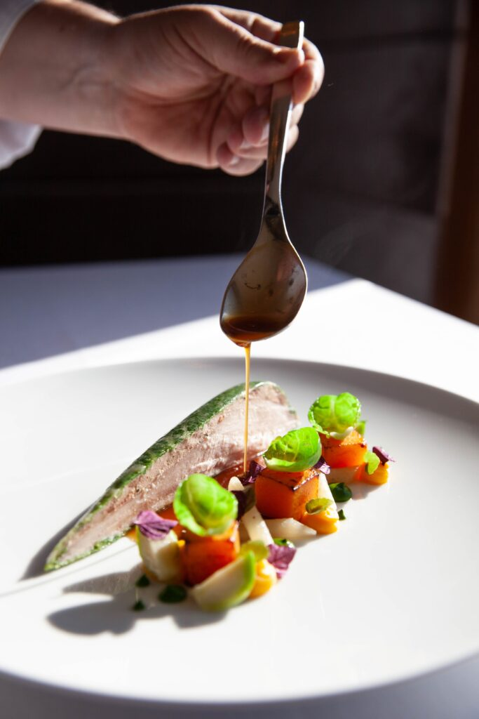chef holding spoon drizzling final touches on a dish