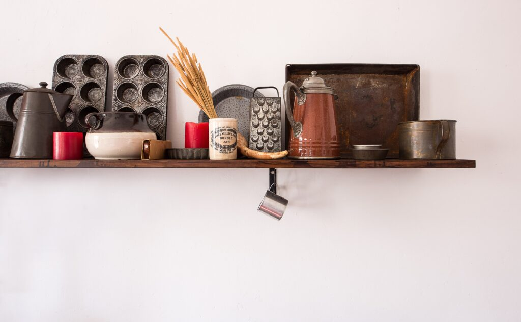 Shelf of kitchen items and cooking tools against white wall