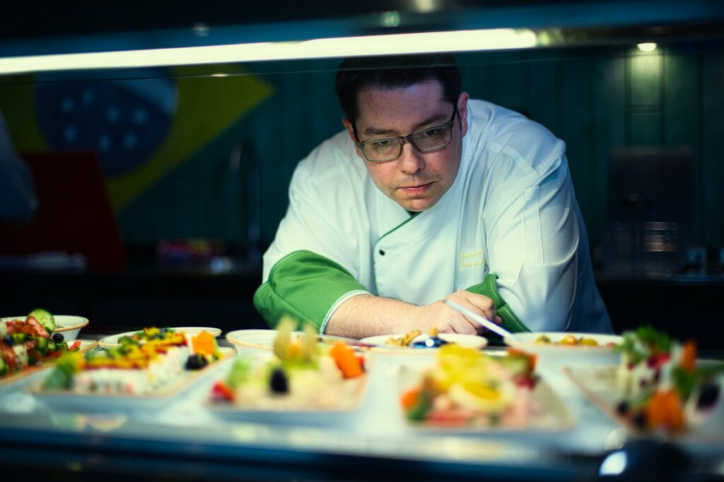 Chef in white uniform looking over several dishes