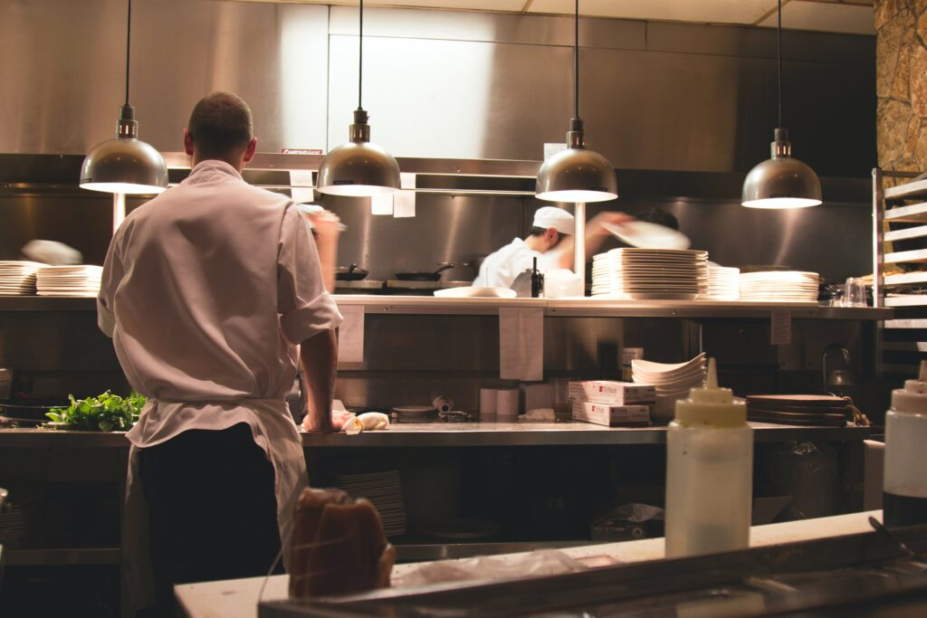 View of a kitchen in a restaurant with multiple chefs working