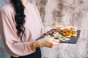 Waitress in pink shirt carrying a plate of sushi to a table