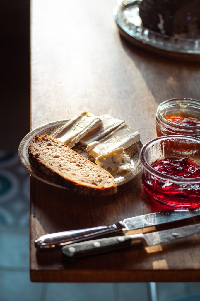 A plate of bread and cheese sitting on a table next to a knife and jar of red jelly.