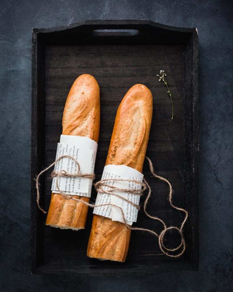 Two French Bread rolls sitting in a box tied up with paper and string.