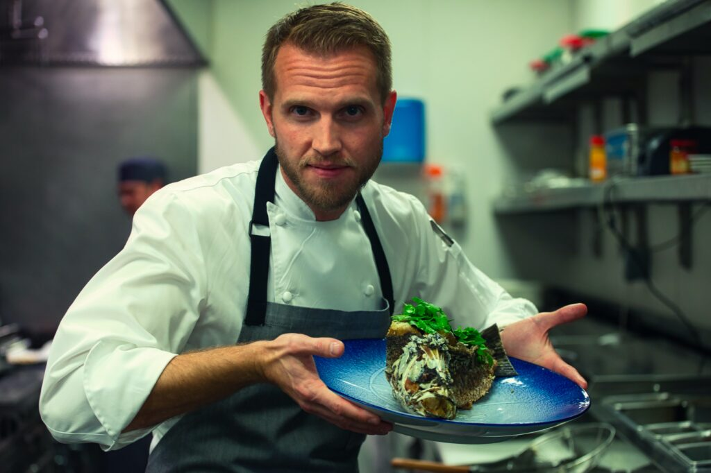 Chef holding plate showing off final dish in kitchen